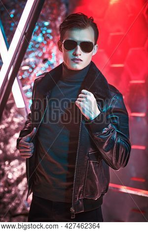 Portrait of a courageous handsome man in black sunglasses and black leather jacket posing among neon lamps. Men's style and fashion. Futurism, techno style.