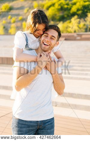 Vertical Portrait Of Happy Young Couple Having Fun In City Park In Summer Sunny Day, Young Woman Han