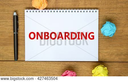 Onboarding Symbol. The Word 'onboarding' On White Note On Beautiful Wooden Table, Colored Paper, Bla