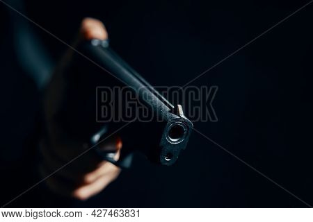 Gun In Mans Hand On Dark Background. Firearms Close-up. Pistol For Attack Or Defense.