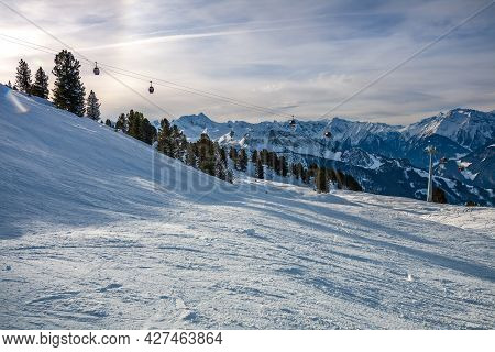 Ski Slope In The Alps Against The Backdrop Of Mountain Peaks And A Cable Car In The Background. Ski