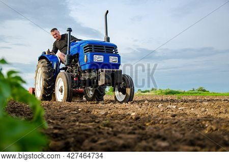 A Farmer On A Tractor Works The Field. Milling Soil, Crushing And Loosening Ground Before Cutting Ro