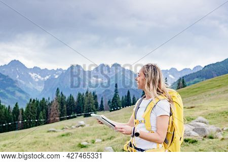 Happy Girl Traveler With Yellow Backpack And Paper Map In The Mountains.