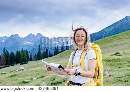 Smiling Female Hiker With Map In The Mountains. Active Recreation.