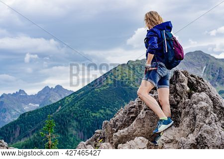 The Rear View Of The Traveler Is Standing On A Rock And Admiring The Beautiful Mountain Views.