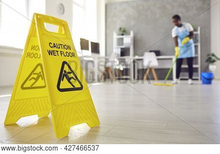 Close Up Of Sign Warning About Wet Floor Placed By Janitor Whos Working In Background