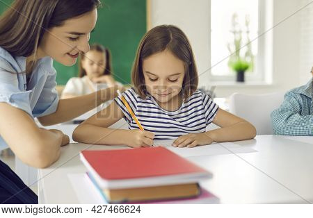 Portrait Of A Little Schoolgirl And A Female Teacher Who Helps To Complete The Task Correctly.