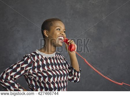 Happy Young Black Woman Holding The Receiver Of Her Landline Telephone And Talking
