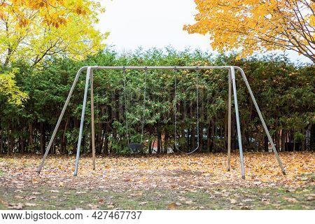 Playground With Swings In The Local Park In Autumn