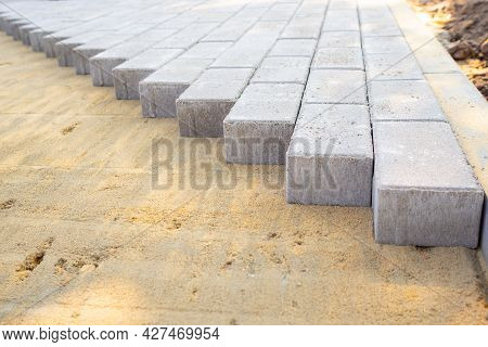 Paving Slabs Or Paving Stones Are Laid Out On The Sand. Process Of Building Footpath. Landscaping, U