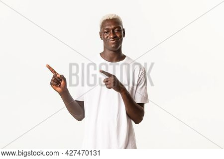 Portrait Of Young African American Blond Guy With Smug Face, Smirking And Pointing Upper Left Corner