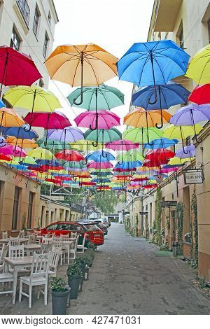 Lodz - Poland. 22 July 2019: Colored Umbrellas Hanging At Top. Set Of Different Umbrellas. Local Lan