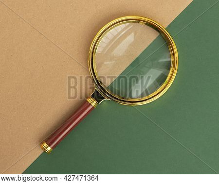 Magnifier On Green And Brown Carton Background. Concept Of Searching And Investigating.