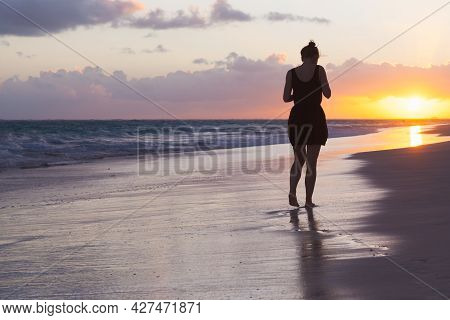 Silhouette Photo Of A Girl Walking At The Atlantic Ocean Coast In Early Morning. Dominican Republic,