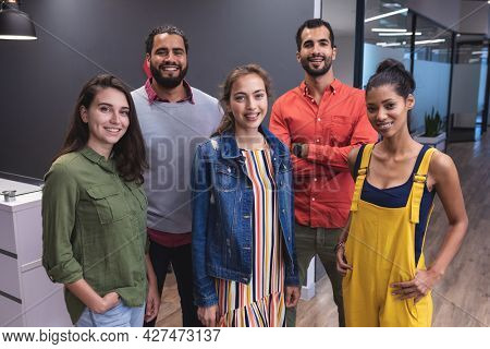 Portrait of diverse group of creative colleagues looking at camera and smiling. modern office of a creative design business.