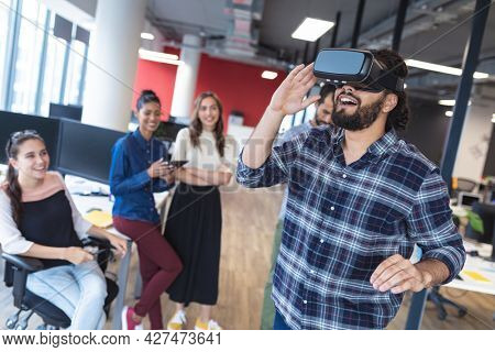 Diverse group of creative colleagues talking at meeting using vr headset. modern office of a creative design business.