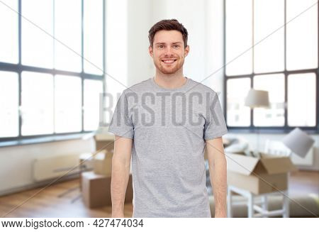 moving, real estate and people concept - happy smiling young man in gray t-shirt and jeans over new home background