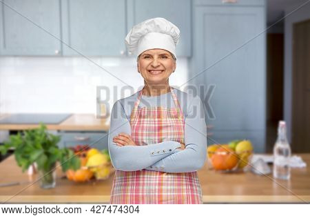 cooking, culinary and old people concept - portrait of smiling senior woman or chef in toque in apron with crossed arms over home kitchen background