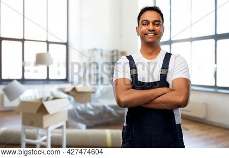 moving, repair and people concept - happy smiling indian worker, loader or repairman with crossed arms over new home background