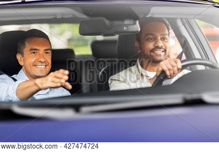 driver courses and people concept - happy smiling car driving school instructor teaching young man to drive
