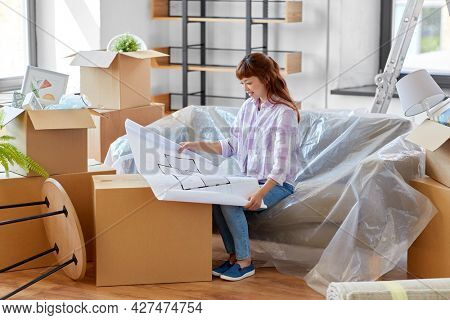 moving, people and real estate concept - happy smiling asian woman with blueprint and boxes at new home