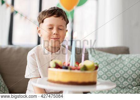 holidays, celebration and people concept - happy little boy with birthday cake making wish at home party