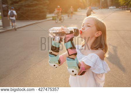 Little Girl Wearing Rollerblading Wrist Guard, Drinking Water Outdoors