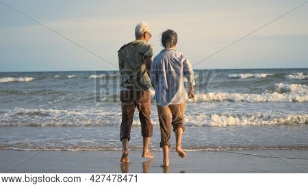 Happy Asian Active Senior Man And Woman Couple Lifestyle Running To Beach And Enjoying Funny, Romant