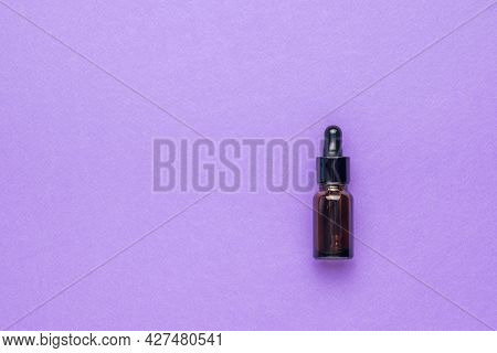 A Small Medical Bottle With A Pipette On A Purple Background. The Concept Of Treatment And Body Care