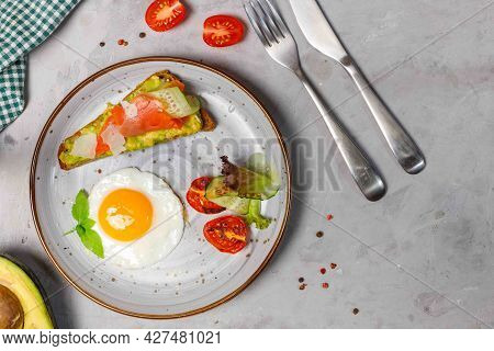 Breakfast With Fried Eggs, Salad And Toast With Salmon, Avocado And Parmesan. Close-up On A Gray Bac