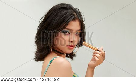 Happy Young Beautiful Woman Applying Makeup On Face By Brush