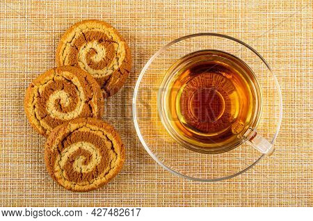 Three Oat Cookies, Transparent Glass Cup With Hot Tea On Saucer On Brown Mat. Top View