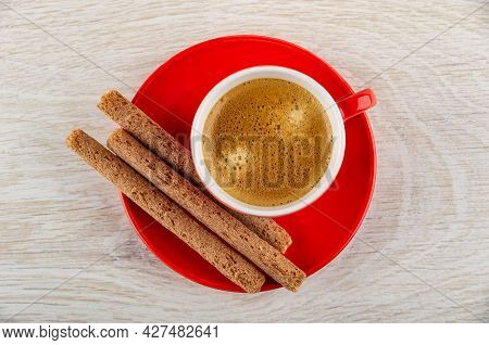 Coffee Espresso In Cup, Crusty Sticks With Cream Filling On Red Saucer On Wooden Table. Top View
