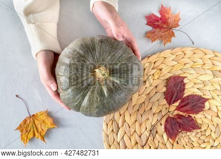 Close-up Of Female Hands Holding A Beautiful Pumpkin On A Gray Surface With Dry Autumn Leaves And A