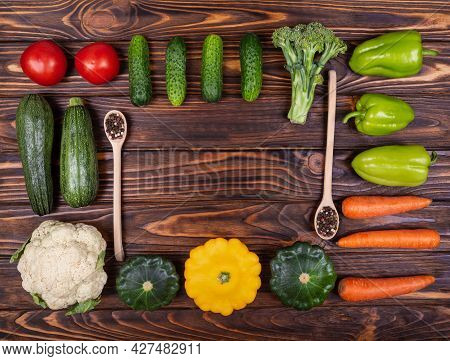 Various Colourful Vegetables On Wooden Background. Bright Vegetables, Spoons, Forks, Knives In Knoll