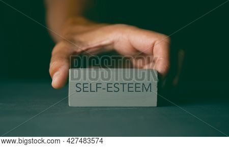 closeup of a caucasian man showing a gray building block with the text self-esteem written in it, on a dark gray surface