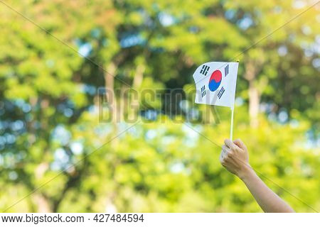 Hand Holding Korea Flag On Nature Background. National Foundation, Gaecheonjeol, Public Nation Holid