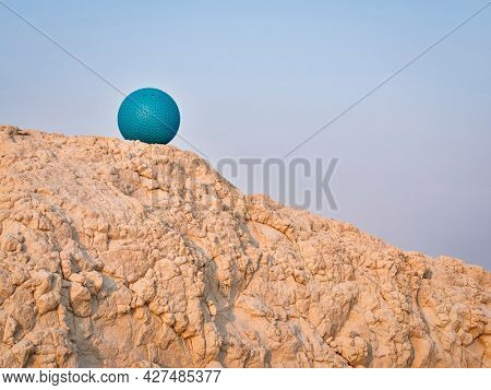 heavy rubber slam ball filled with sand on at a clay cliff, outdoor exercise and fitness concept