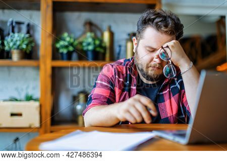 Photo Of An Exhausted Man Working At Home Before The Deadline.