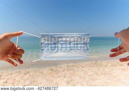 Widely Stretched Medical Mask In Human Hands Against The Background Of The Sea. Imitation Of Putting