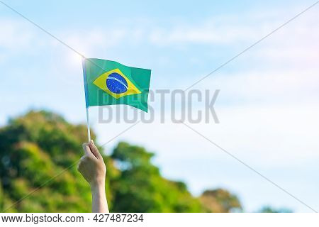 Hand Holding Brazil Flag On Blue Sky Background. September Independence Day And Happy Celebration Co