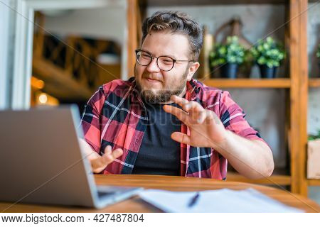 Photo Of A Friendly Young Man In In Front Of Laptop Monitor During Online Video Call.