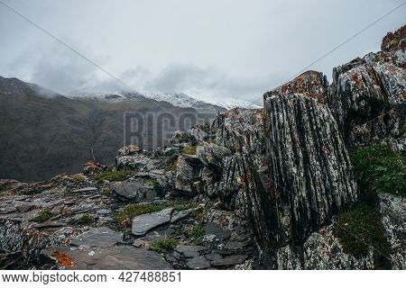 Atmospheric Highland Landscape With Pointy Stones And Snowbound Mountain In Overcast Weather. Sharp