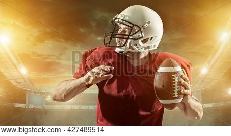 American football sportsman player with ball in action on stadium under lights of background. Sport, proud footballer in white helmet and in red, ready to play.