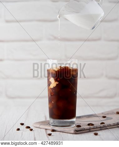 Iced Coffee Latte Cappuccino In A Tall Glass With Cream Or Milk Poured Over Andcoffeebeans And Str