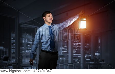 Happy Businessman Holding Glowing Lantern On Background Office Interior. Young Man In Shirt And Tie