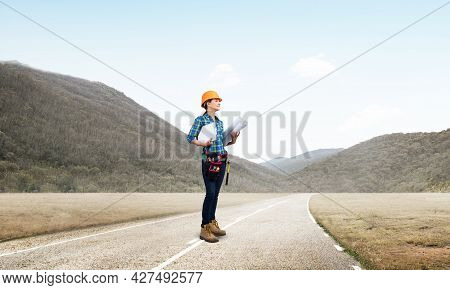 Young Woman In Safety Helmet Standing On Asphalt Road With Blueprints. Female Architect In Workwear