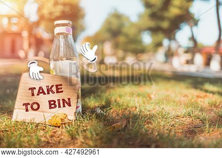 The Concept Of Environmental Pollution And Waste Sorting. A Glass Bottle With Cartoon Hands Holds A