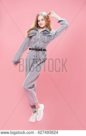 Full length portrait of a smiling girl teenager posing in fashionable denim overalls on a pink background. Studio fashion shot. Youth style.