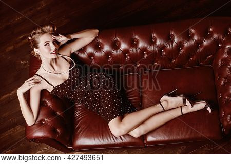 Full length portrait of a beautiful glamorous woman with pin-up hairstyle and make-up lying on a leather sofa in elegant evening dress. Pin-up beauty and fashion concept.